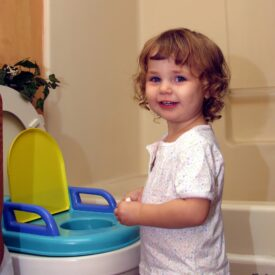 Toddler smiling next to her potty seat
