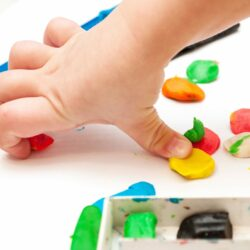 Child moulds from plasticine on table. hands with plasticine. Little girl is learning to use colorful play dough