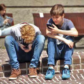 2-boy-sitting-on-brown-floor-while-using-their-smartphone-2