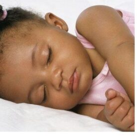 pretty african american baby in pink sleepying